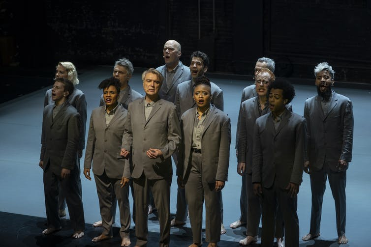 A group of people in grey suits sing out towards the audience.