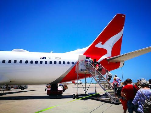 Passengers board a Qantas plane