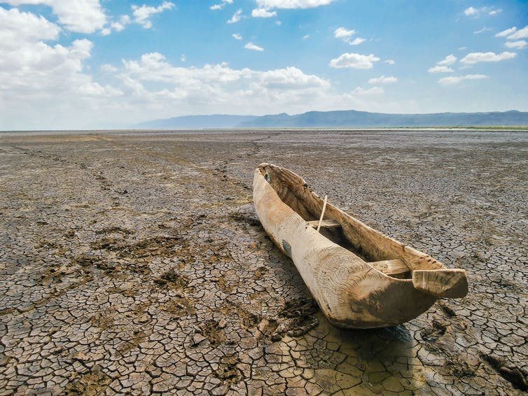 An old wooden fishing boat on a dried up river bed.