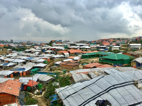 View of many makeshift coloured buildings under grey sky.