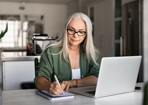 A woman studying using a laptop and taking notes