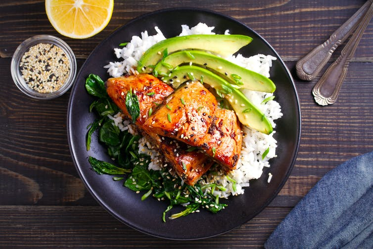 A plate of cooked salmon with rice and avocado.