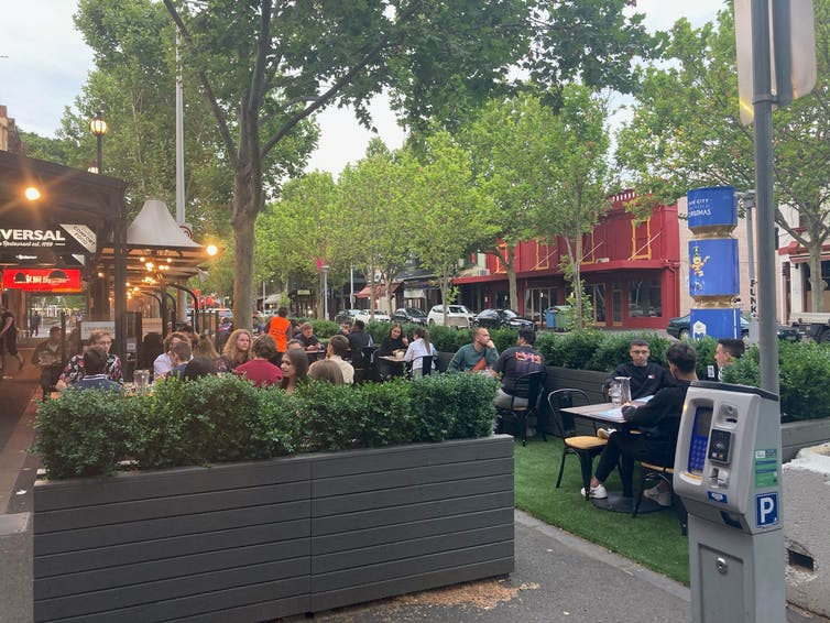 Diners sit within a green parklet on Lygon Street in Melbourne, having fun on reclaimed street space.