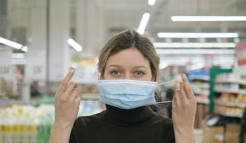 A young woman puts on a face mask in a supermarket.