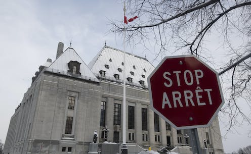 The snow-covered Supreme Court of Canada is seen with a stop sign in the foreground.