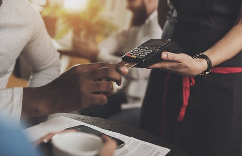 A Black customer inserts a credit card into a point of sale device held by a white waiter.