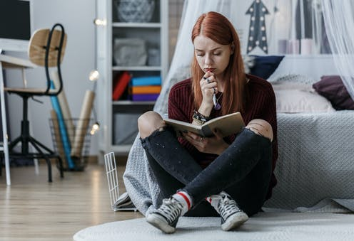 Girl in bedroom writing diary