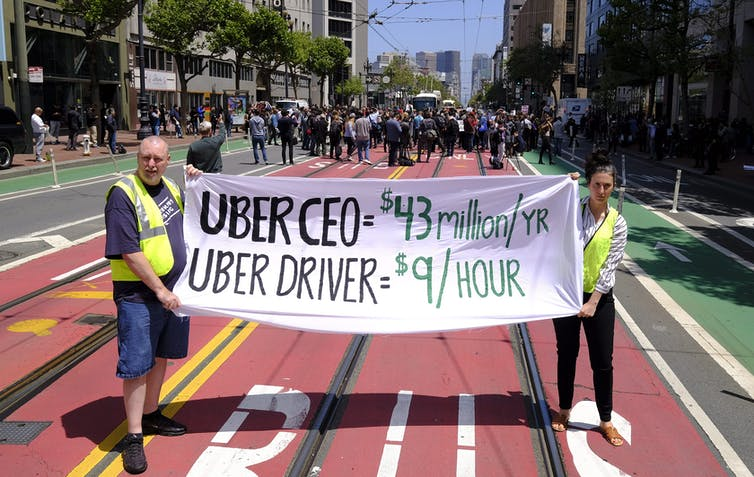 Two people hold up a sign decrying low wages for Uber drivers on a city street.