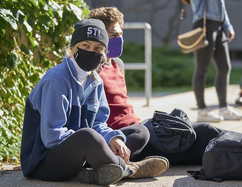 Two casually dressed young people in face masks sit on the ground with their backpacks beside them.