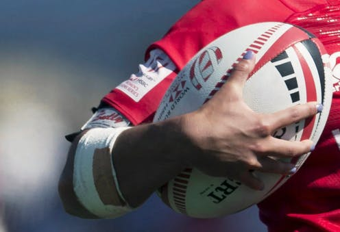A closeup of a woman holding a rugby ball in her arm.