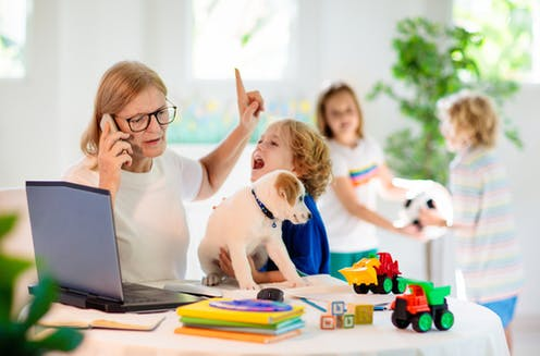 Mum working from home while kids demand attention