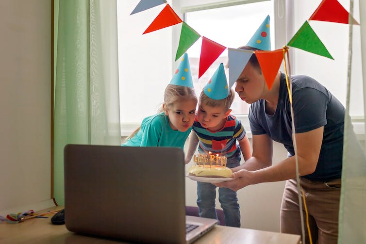 Father holding birthday cake in front of computer screen with children for a Zoom birthday party