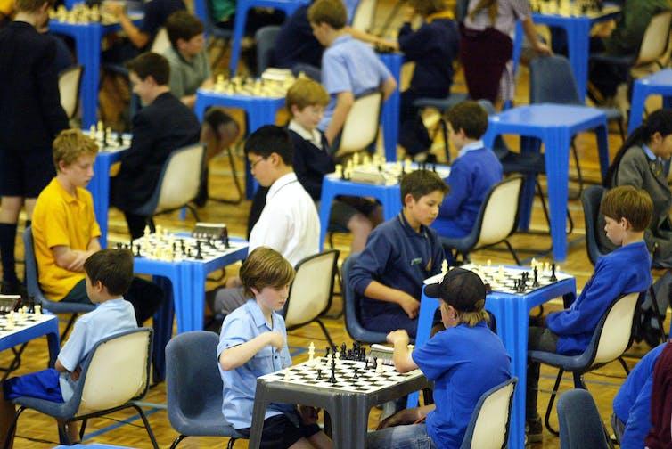 Children play chess in school uniform.
