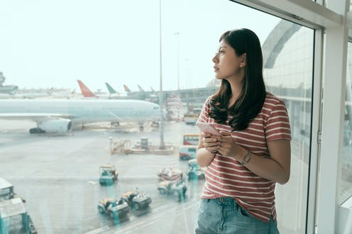 Young Chinese women looks out of airport window