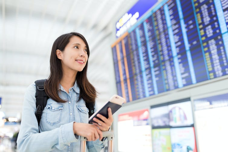 Young Chinese women looks up at airport departures board