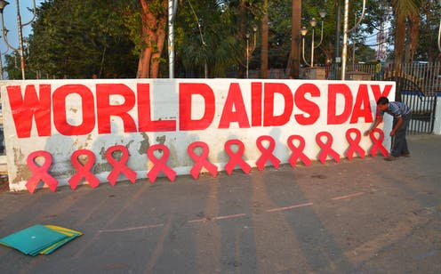 Man arrange red ribbon symbols in front of World AIDS Day mural.