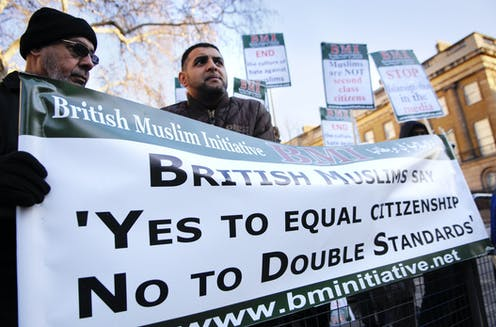 British Muslims holding banner reading 'British Muslims say yes to equal citizenship no to double standards'.