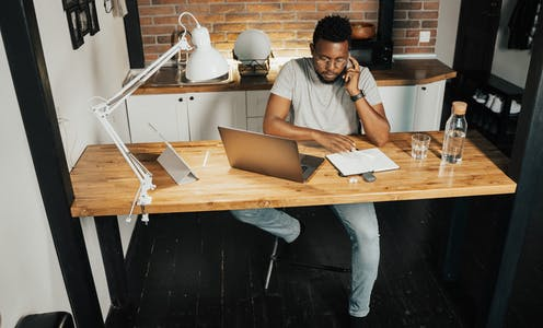 A man sits at his kitchen counter with his laptop and a notepad.
