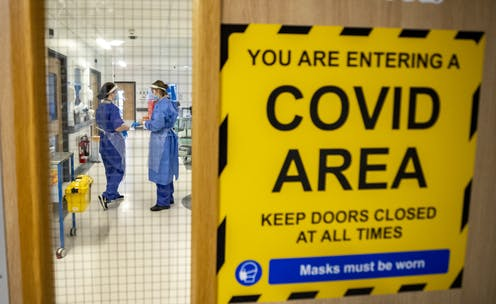 "Two healthcare workers in full PPE seen through a door bearing a sign saying ""YOU ARE ENTERING A COVID AREA"""