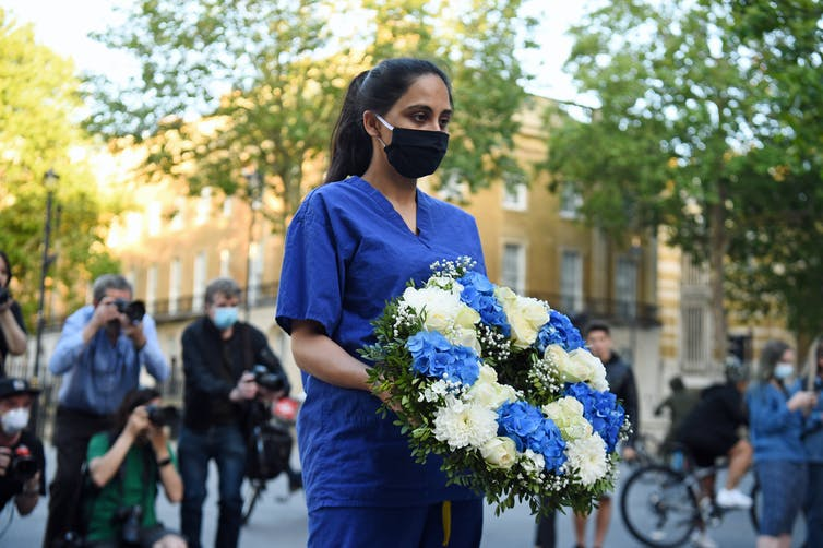 A woman wearing hospital scrubs and a mask carries a wreath of flowers.