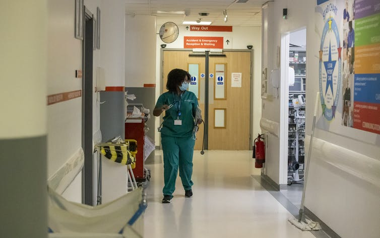 A woman wearing scrubs stands in a hospital corridor.