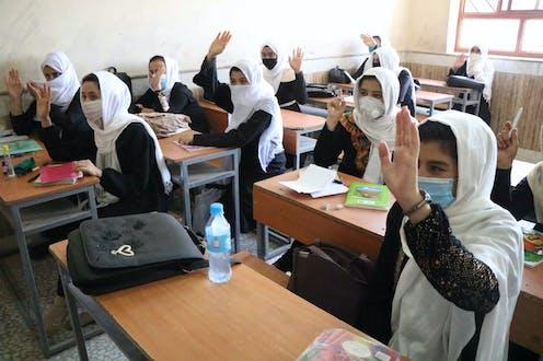 Afghan schoolgirls in a classroom wearing COVID masks.