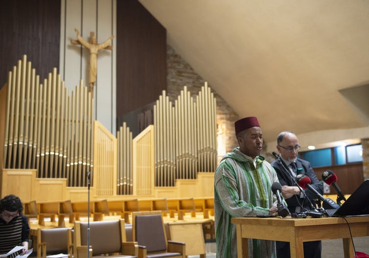 Two Muslim men stand in a church's pulpit.