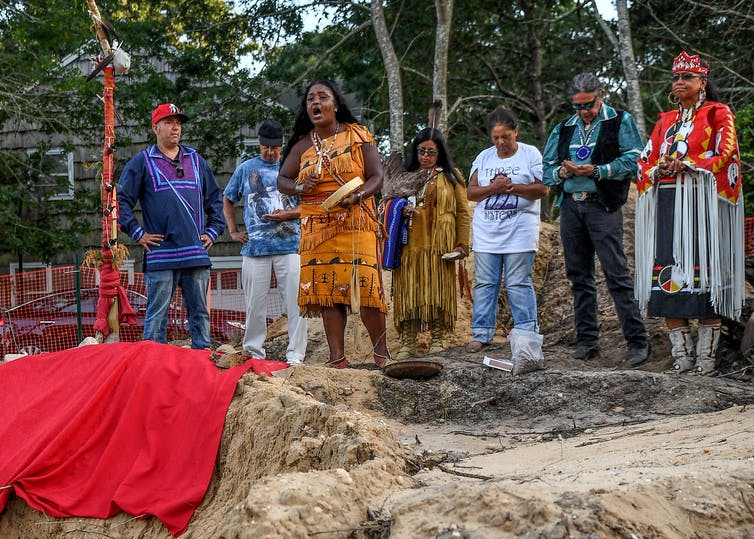 Shinnecock tribe members hold a prayer service on a site where human remains, likely belonging to the Shinnecock Nation, were unearthed.
