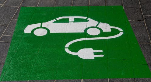 Stenciled sign on pavement of electric vehicle.