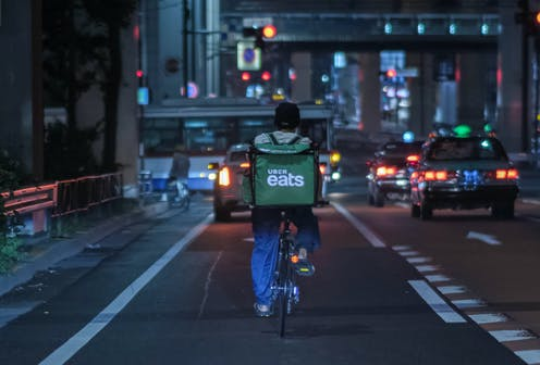 Food delivery rider cycles down busy city street at night