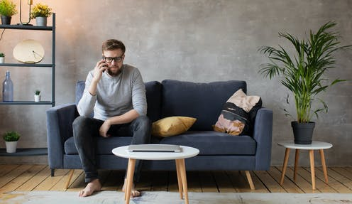 Man sits on the couch at home talking on the phone.
