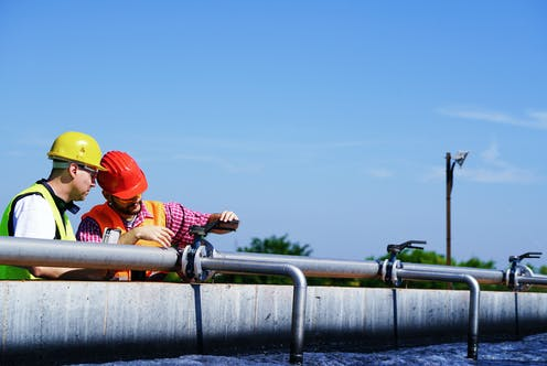 Two men testing water at a sewage treatment plant