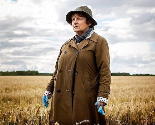Shabbily dressed woman in field