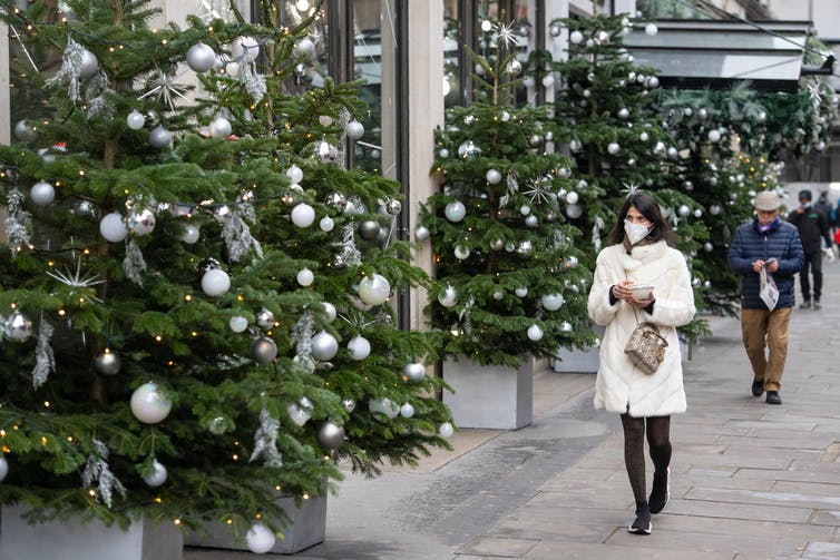 A woman walks past a display of Christmas trees.
