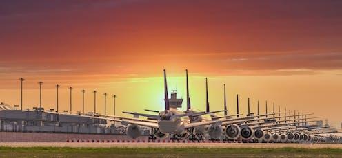 Aviones aparcados en línea durante la puesta de sol.