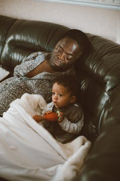 A man is asleep on the sofa with his small child who is awake watching something.
