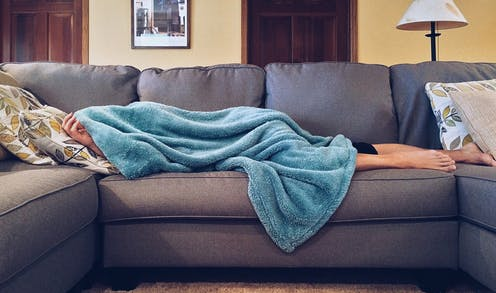 A person lying a sofa, almost entirely covered by a fluffy blue blanket