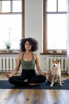 A woman and her dog on a yoga mat.