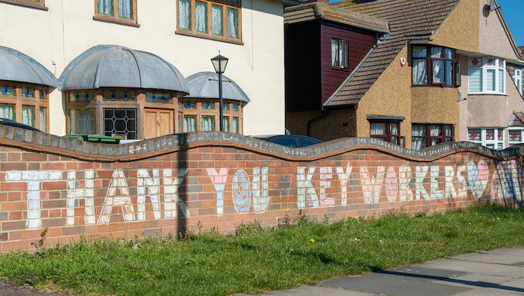 'Thank you keyworkers' written in large chalk letters on wall in front of houses.