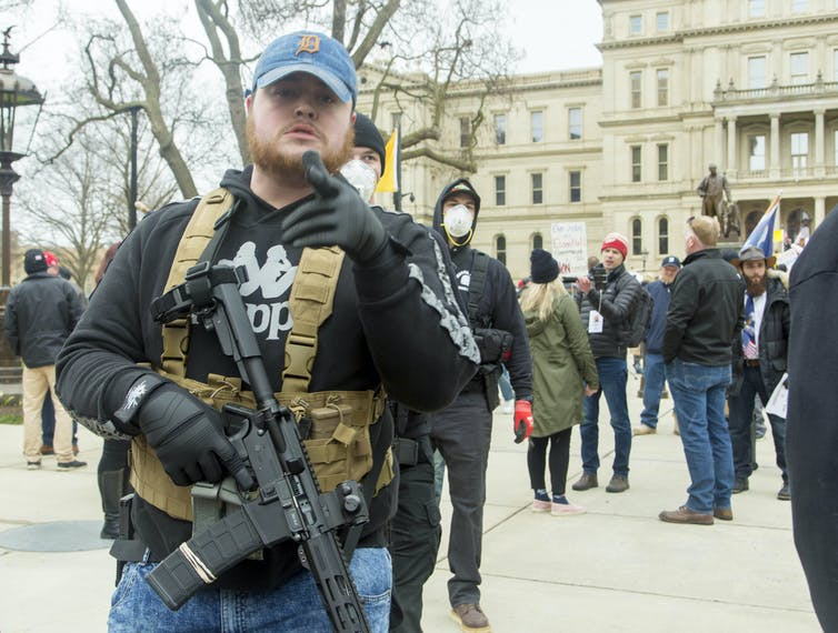 Men dressed in quasi-military outfits and carrying guns at a protest in Lansing, Michigan in April 2020.