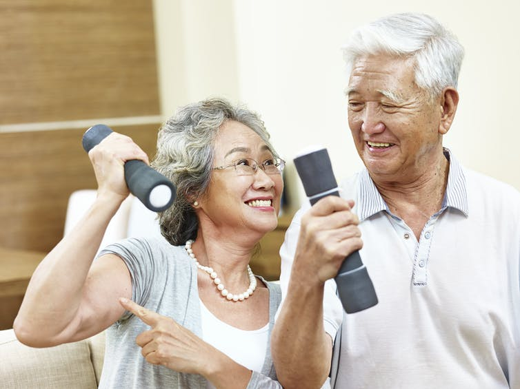 A man and a woman with gray hair with small dumbbells in their hands.