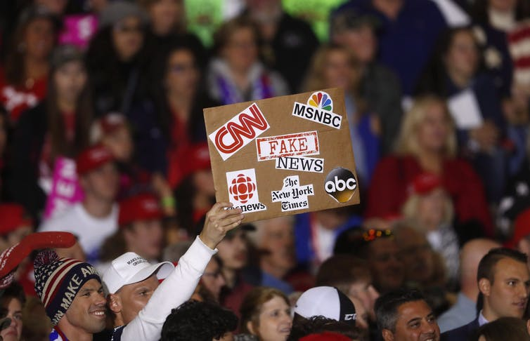 A Trump supporters holds up a fake news sign during a Trump rally.
