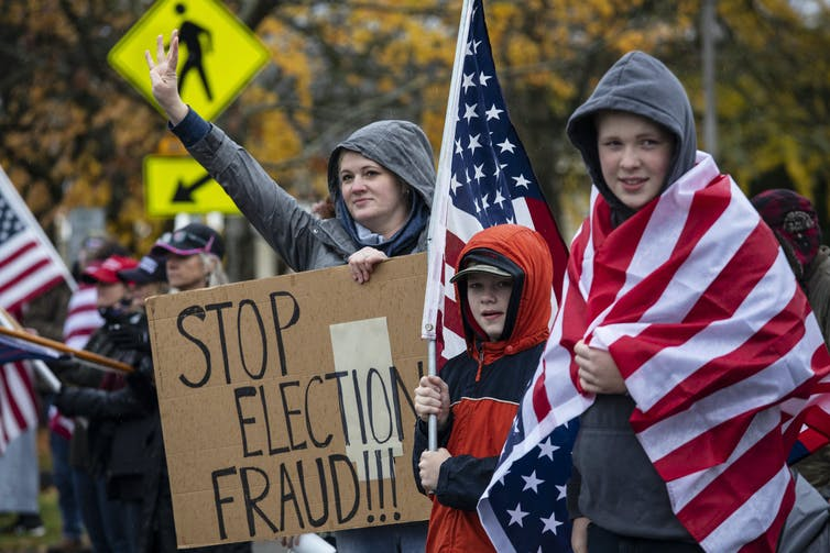 A woman and two children dressed in rain jackets hold up a Stop Election Fraud sign