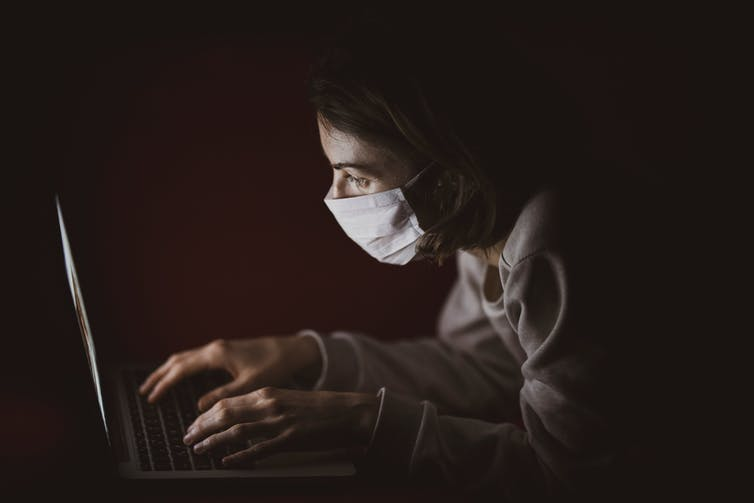 Person in mask looks at laptop in darkened room