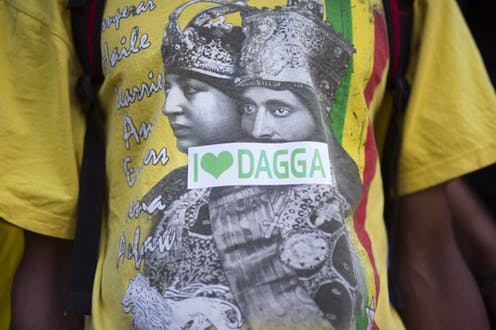 A T-shirt with an image of Ethiopian rulers in black and white and a sticker in green and white across it reading, 'I love dagga'.