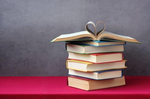 Pila de libros. El superior abierto con varias hojas formando un corazón.
