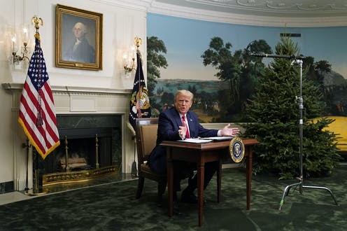 Donald Trump sits at a noticeably small desk at the White House