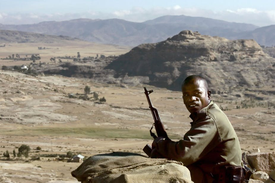 A dressed in green military and armed with an AK-47 rifle keeps watch over a mountanious area