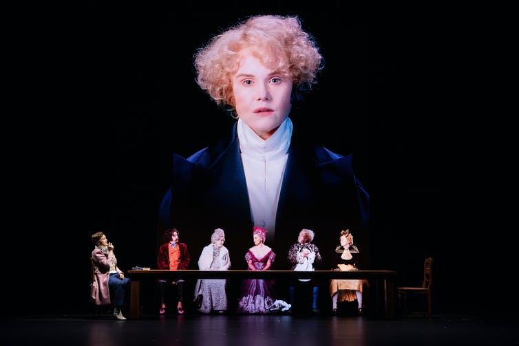 Woman projected on screen behind women seated onstage.