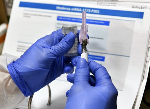 Gloved hands holding a syringe and vaccine vial